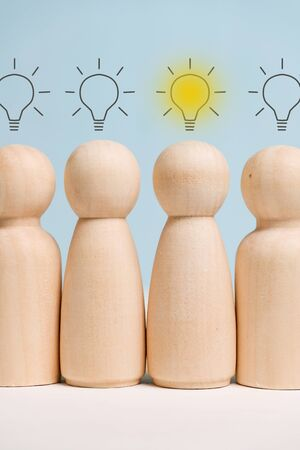 Wooden figures standing in a row with light bulbs above them. Concept of birth ideas. Close up. Vertical.