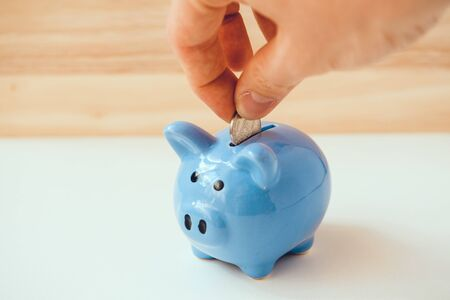 Hand is putting coin in blue piggy bank on wooden and white background. The concept of saving.