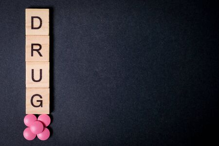 The word drug is on wooden squares next to pink tablets on a black background. Copy space. Top view. Close up.