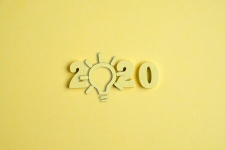 Creative idea concept in the new year 2020. A yellow light bulb next to the numbers on the yellow background. Close up. Imagens