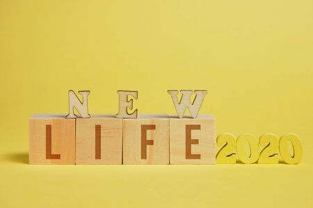The concept of a new life. Wooden numbers 2020 next to cubes with letters on a yellow background. Close up.