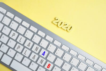 Wooden figures 2020 with a keyboard with the inscription Plan A and Plan B on a yellow background. Close up.