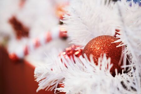 Red ball Christmas decorations with white tree branches. Close up.