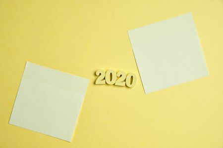 The figures are wooded by 2020 next to stickers on a yellow background. Close up. Top view. Imagens