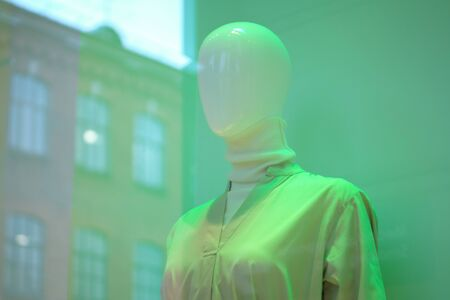 Mannequin behind glass on shop window in green shades. Close up. Stock fotó
