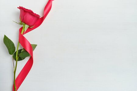 A beautiful red rose with a ribbon on a white wooden background. Top view. Copy space. Close up.