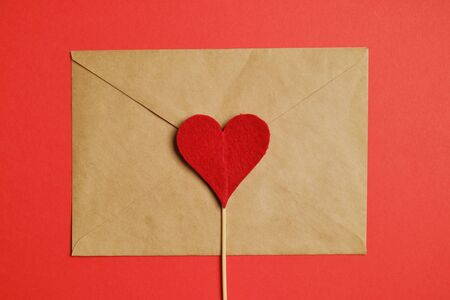 Red heart on a stick with a craft envelope on a paper background. Top view. Close up. Stock fotó
