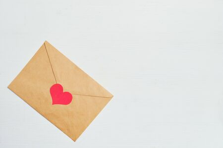 Red heart with a craft envelope on a white wooden background. Top view. Copy space. Close up.