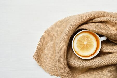 A white cup of tea with lemon in linen on a white wooden background. Copy space. Top view. Close up. Stock Photo
