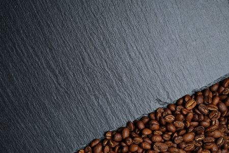 Coffee beans next to the slate board. Top view. Close up. Copy space.