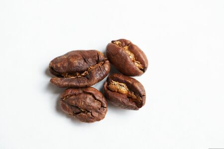 Bad coffee beans on a white background. Close up.