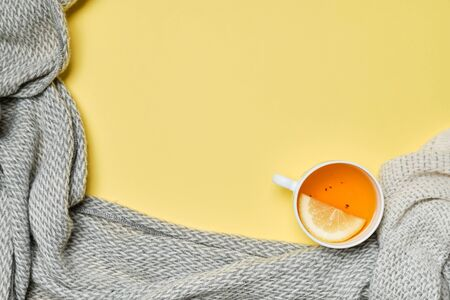 A cup of tea with a lemon and a scarf on a yellow background. Copy space. Top view.
