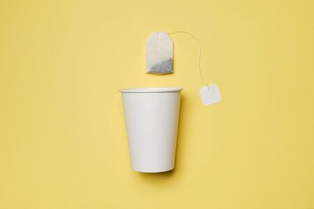 White cardboard cup with tea bag on a yellow background. Mock up. Copy space. Top view.