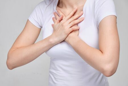 A girl in a white T-shirt suffers from chest pain. Difficulty breathing. Close up.