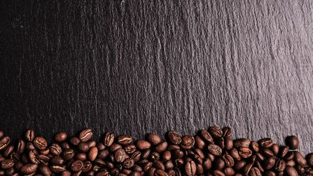 Coffee beans on a slate board. Copy space..