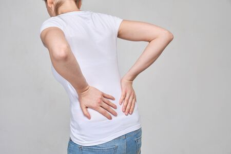 A girl in a white T-shirt massages her lower back from severe pain. Sciatica, sciosis. Close up.
