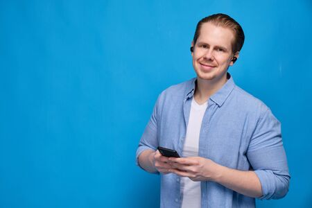 A man in a blue shirt dressed wireless headphones holds a smartphone and looks at the camera. The concept of ease of communication and modern technology. Close up.