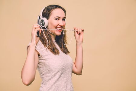 Girl in a T-shirt on a yellow background listens to music in a white earphone. The concept of a profitable paid subscription for listening to audio. Toned. Close up.