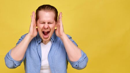 A man in a blue shirt on a yellow background screams strongly and hands near his head. The concept of crazy discounts on sale. Close up.