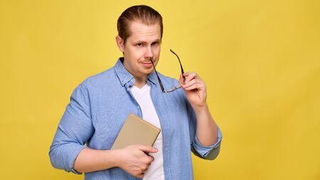 A man in a blue shirt on a yellow background holds glasses and a book. The concept of a researcher at the institute. Close up. Banque d'images