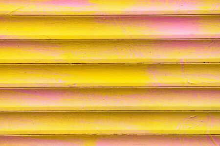 Background and texture of metal gates in yellow and pink colors. Close up.