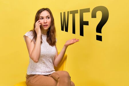 A girl in summer clothes on a yellow background sits and swears on the phone - the word WTF. Close up. Banque d'images