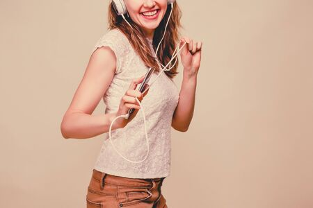 A girl in summer clothes stands on a yellow background, listens to music in white headphones, holds a smartphone and dances. Toned. Close up.