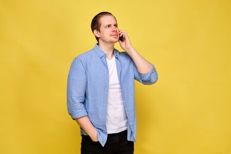 A man in a shirt on a yellow background listens for a voice message through a smartphone. Close up.