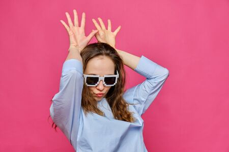Stylish caucasian girl in a pale blue t-shirt and 8-bit glasses and makes bunny ears with his hands on a pink background. Close up.