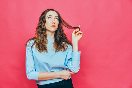Stylish caucasian girl in a pale blue t-shirt on a pink background. Concept dream and wish for something. Close up.