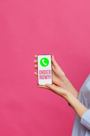 Girl hand holds a smartphone with a handset icon and the inscription order now on a pink background. Close up.