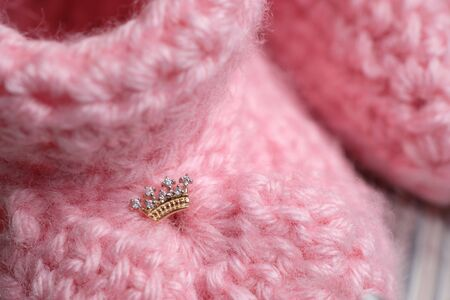 Small earrings in the shape of a crown on booties. Close up,