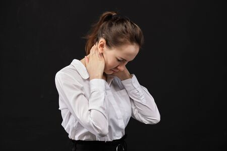 Girl office employee massages her neck from fatigue. Close up.