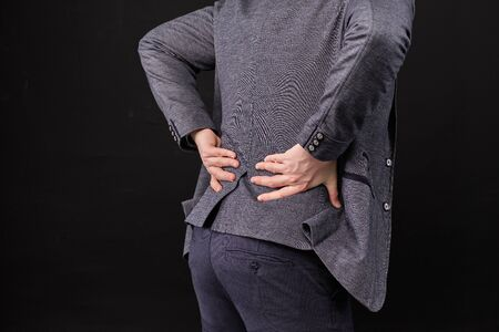 A man in a jacket massages the lower back with his hands on a black background. Close up.