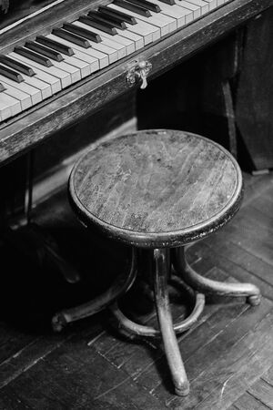 Old piano and chair. Black and white photo. Close up. Noise.