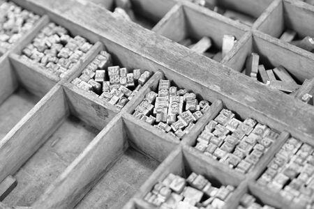 Old metal letters for printing black and white photo. Close up. Noise.