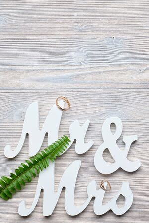 White letters mr and vhk on a wooden background with a ring and a green branch. Top view. Copy place. Close up.