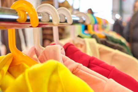 A stand with hangers of fashionable children hoodies, sweatshirts. Close up. Foto de archivo