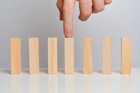 The concept of emphasis on the business process. Hand holds wooden blocks on a white background. Close up.