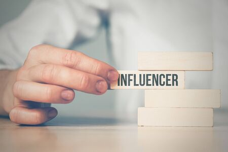 Influencer concept - hand holds wooden blocks with the inscription. Close up.