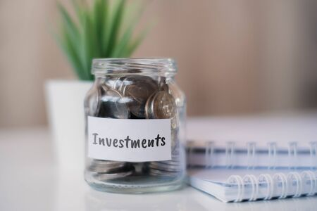 The concept of accumulating money for investments - a glass jar with coins. Close up. Stock Photo