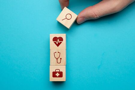 Medical care search concept with icons on wooden blocks. Close up.