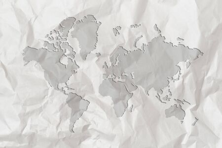 A map of the world is depicted on crumpled white paper. Close up.