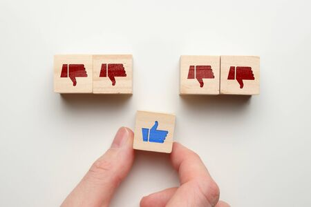 Like dislike concept on wooden cubes with hand. Close up.