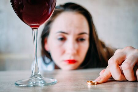 A drunk girl with a glass of wine is sad because of a divorce from her husband. Close up. Foto de archivo