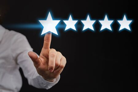 The hand points to five 5 stars as a concept of top rating or rating. Close up.