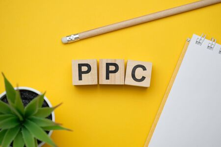 Modern marketing buzzword PPC - Pay per click. Top view on wooden table with blocks. Top view. Close up.
