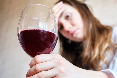 A woman is sitting on a sofa with a glass of wine.