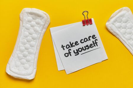 Women's pad with a sticker and the inscription take care of yourself on a yellow background