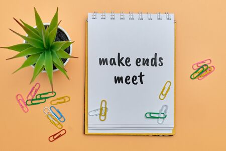 make ends meet - english money idiom hand lettering on wooden blocks